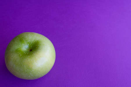Green apples on purple background. Color trends concept with copy space