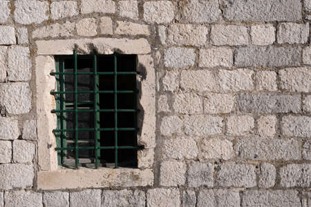 Old window with bars, in an ancient medieval wall