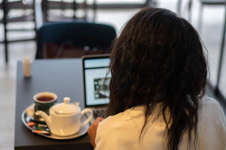 Young businesswoman drinking tea and using tablet computer in cafe. Back view. 写真素材