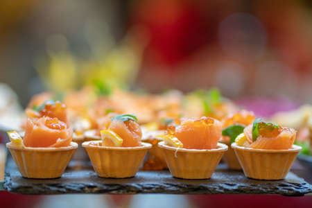 Tartlets with red fish and caviar. Close-up of gourmet food.