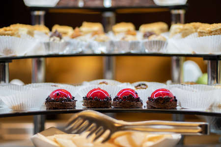 Mix of sweets, cakes, muffins. Beautifully laid out on a glass showcase. Setout.