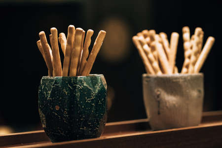 Bread sticks in a ceramic bowl on a wooden table. 写真素材