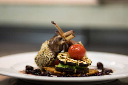 Beautifully decorated rack of lamb with vegetables and sauce.