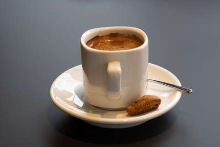 Cup with coffee and cookies on a dark gray table.