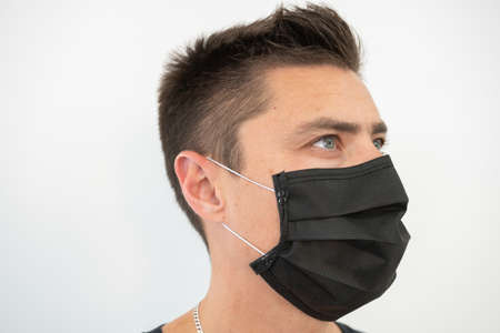 Black protective mask on the young guys face, portrait.