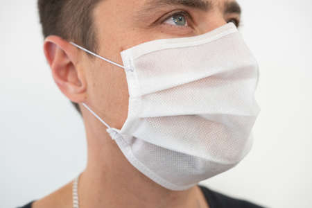 White protective mask on the young guys face, portrait.