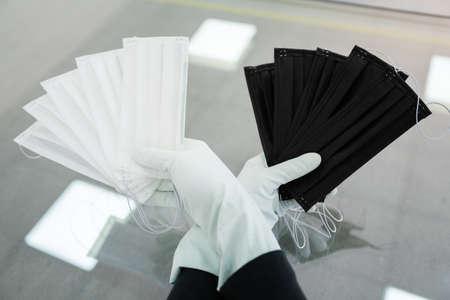Man holds rubber gloves black and white face masks. 写真素材