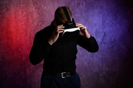 Brutal man wearing virtual reality goggles in studio. Using with VR headset.