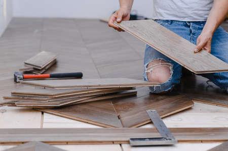 Man laying parquet flooring - closeup on male hands. worker joining parquet floor Stock fotó
