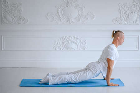 Man practicing advanced yoga against a white background