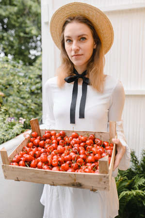 happy woman with cherries wearing hat and white dress. Healthy eating, dieting, vegetarian food and people concept