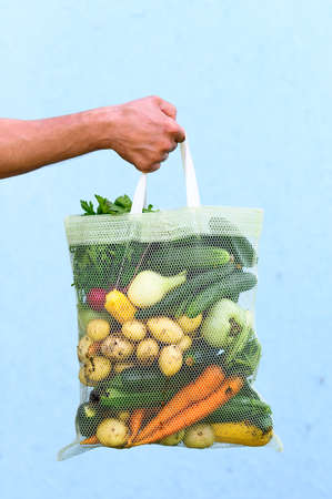 Eco friendly reusable shopping bag filled with fresh farm vegetables on a blue background.
