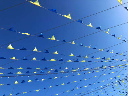 A row of decorations small flags fluttering in the wind against the background of a deep blue sky