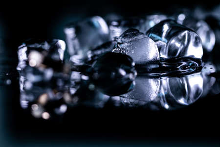 pile of different ice cubes on reflection table on black background