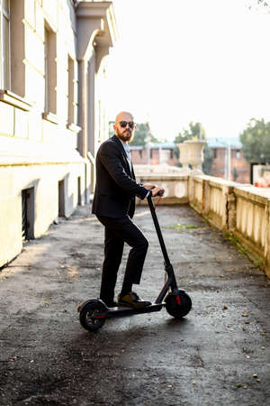 Attractive business man riding a kick scooter at cityscape background Banco de Imagens