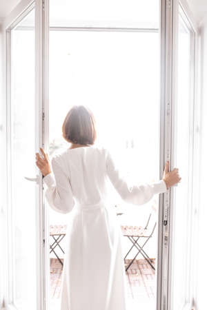 girl in white dress opens the door to the balcony. wedding day