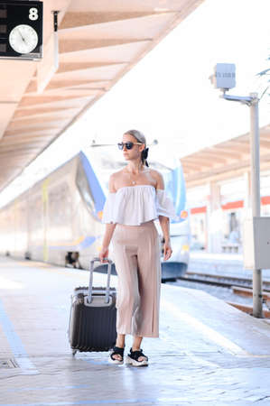 Elegant young woman with luggage at a train station. tourism concept Reklamní fotografie