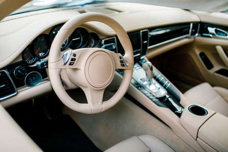 Wide view of modern car interior with light-colored decoration
