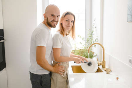 young happy couple is washing dishes while doing cleaning at home Stok Fotoğraf