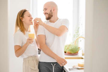 Loving man feeding happy woman showing care cooking healthy meal together on weekend, happy romantic funny couple 版權商用圖片