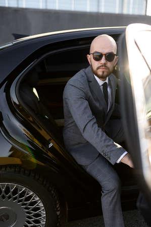 Business man in suit opening black car door