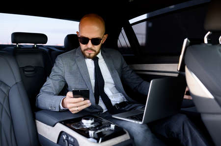 Gut aussehender Geschäftsmann mit seinem Handy in einem modernen Auto mit einem Fahrer im Zentrum der Stadt. Geschäftskonzept, Erfolg, Reisen, Luxus