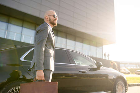 businessman on the background of an expensive car on a sunny day