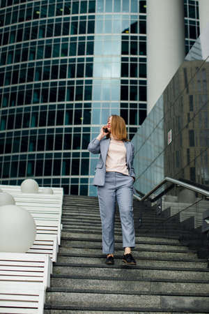 business woman talking on the phone in the background of an office building