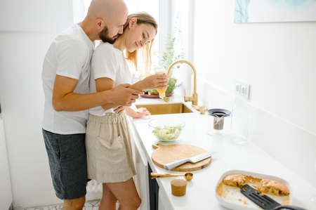 Young happy couple having breakfast at home together