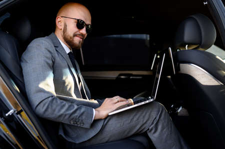 businessman working on laptop in back seat of Executive car. Concept of business, success, traveling, luxury.