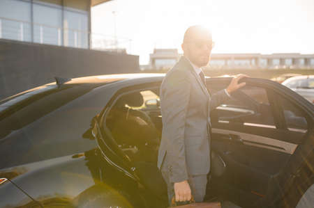 Portrait of a handsome businessman in sunglasses standing near the car outdoors in front of the modern building facade Stok Fotoğraf