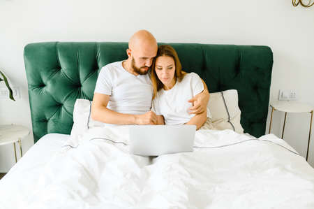 young couple using laptop together in bed