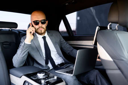 handsome businessman using his mobile phone in a modern car with a driver in center of the city. Concept of business, success, traveling, luxury Stok Fotoğraf