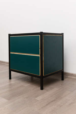 Green chest of drawers on a white wall background