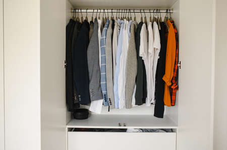 Many mans clothes in wardrobe, closeup.