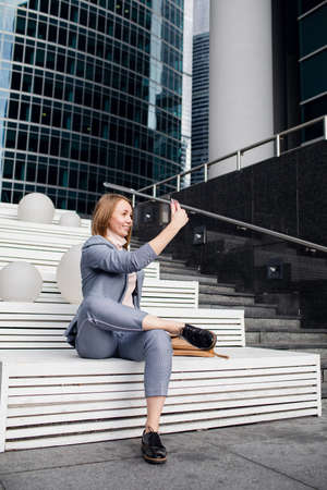 young girl in a business suit takes a selfie on the stairs.