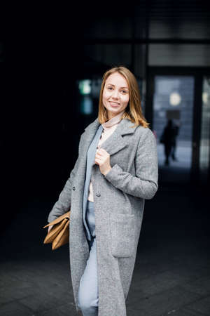 young girl in a business suit on a dark background of office buildings. Stok Fotoğraf