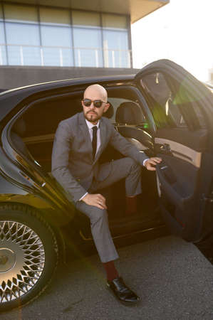 a bald business man with beard in an expensive suit in an expensive car