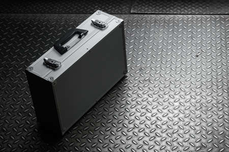 The aluminum iron suitcase with locks on a metal background
