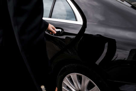 Close up of a man opening a car door. Black luxury car Stockfoto
