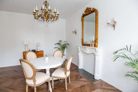 White living room with classic decor, mirror, fireplace, dining table Banque d'images