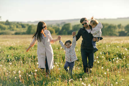 Happy young family spending time together outside in green nature Stock Photo - 137255536