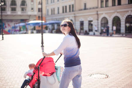 young mother walking with baby in stroller