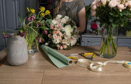 Handsome fresh bouquet. Flowers delivery. Woman florist create flower arrangement in a wicker basket. Beautiful bouquet of mixed flowers. Floral shop concept . Banco de Imagens - 137889928