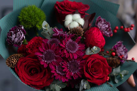 Close-up flowers in hand. Florist workplace. Woman arranging a bouquet with roses, chrysanthemum, carnation and other flowers. A teacher of floristry in master classes or courses