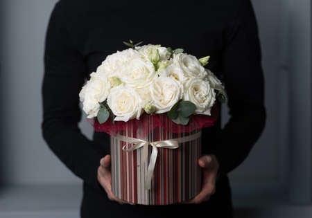 Cute little floral arrangement of mixed flowers in man hand. Round box. The work of the florist at a flower shop. Delicate Pastel color. Fresh cut flower Banco de Imagens - 137889841