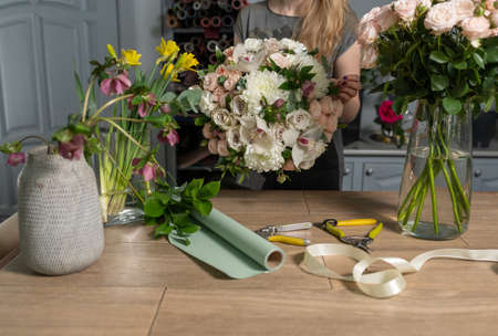 Handsome fresh bouquet. Flowers delivery. Woman florist create flower arrangement in a wicker basket. Beautiful bouquet of mixed flowers. Floral shop concept . Banco de Imagens - 137890009