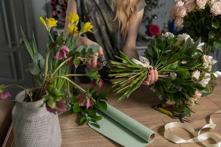 Handsome fresh bouquet. Flowers delivery. Woman florist create flower arrangement in a wicker basket. Beautiful bouquet of mixed flowers. Floral shop concept . Banco de Imagens