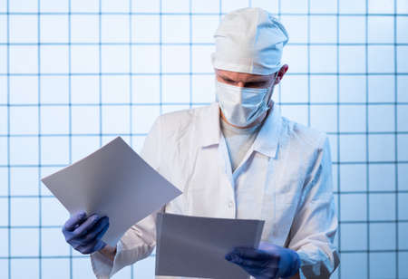 Male Doctor with files on hospital holding clipboard and writing a prescription. Healthcare and medical concept, test results.
