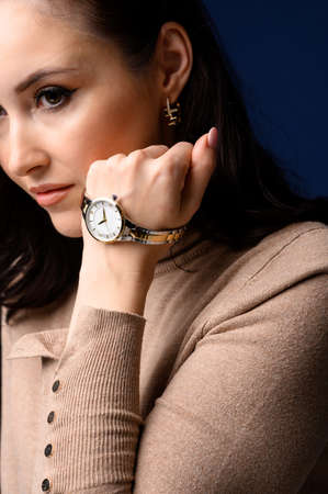 Close up portrait of middle age beautiful fashionable woman posing. Model wearing wrist watch. Female fashion concept